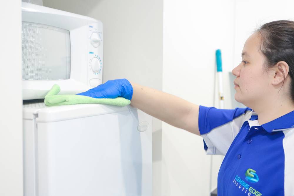 Cleaner wiping the top of a fridge with the correct coloured cloth.