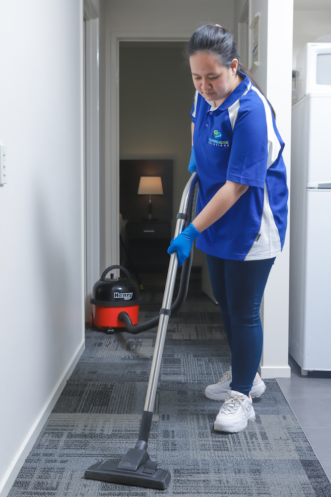 Cleaner vaccuming a carpeted hallway.