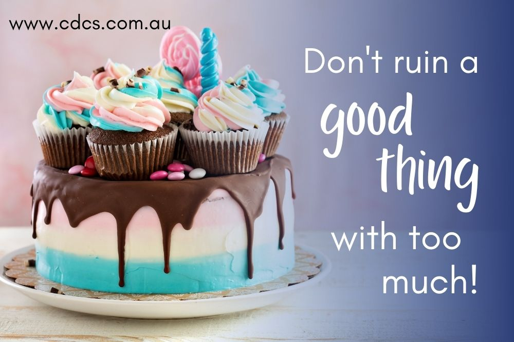 A beautifully decorated cake in blue, white and pink, with text: Don't ruin a good thing with too much!