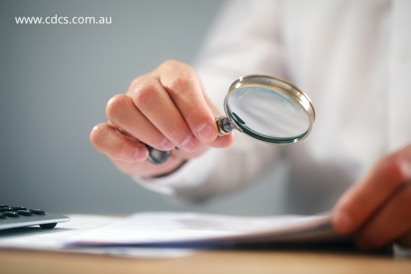 Businessman reading documents with magnifying glass