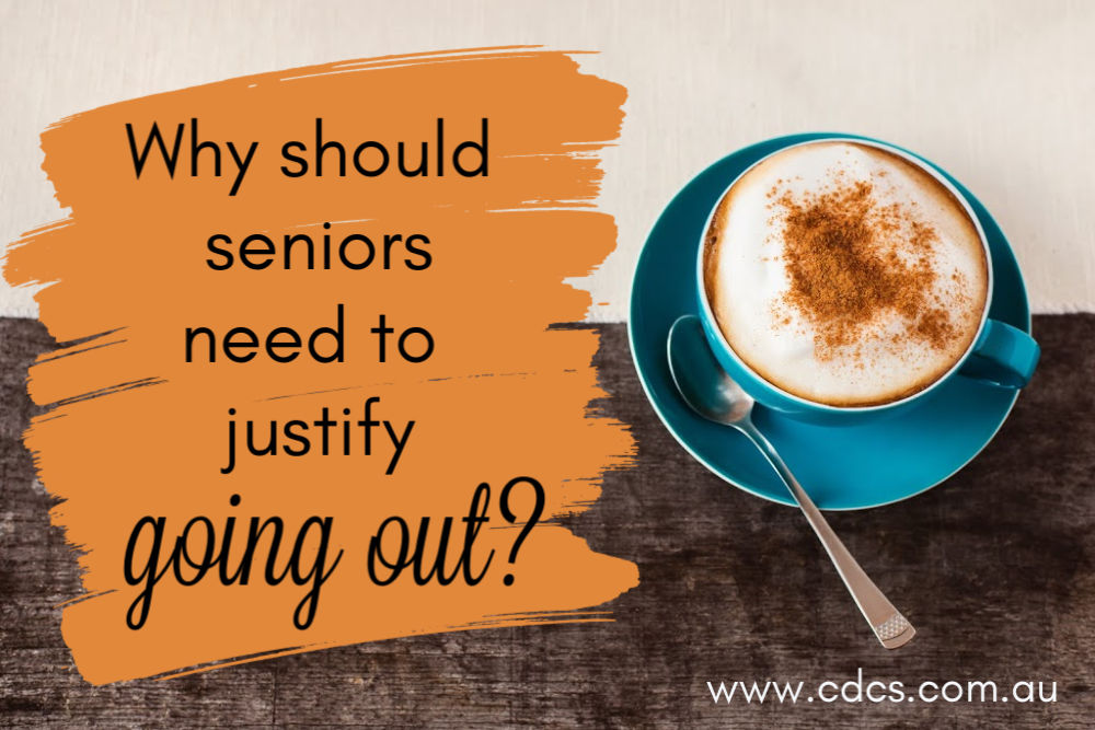 "Two cups of coffee on a wooden table background, text says ""Why should seniors need to justify going out?"""